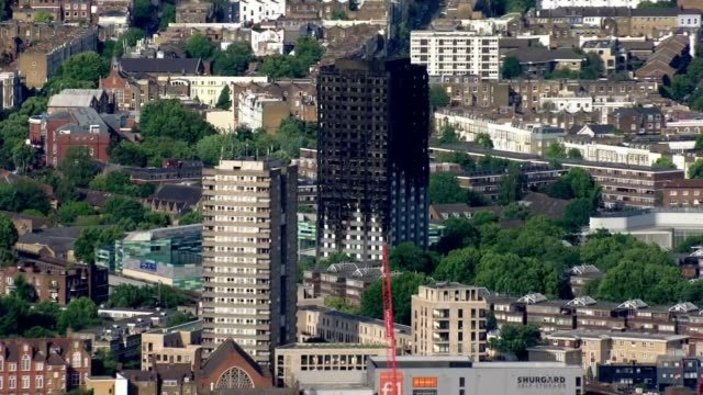 stockvideo's en b-roll-footage met one of the final funerals of victrims held date unknown west london burnt out shell of grenfell tower block of flats - kensington en chelsea