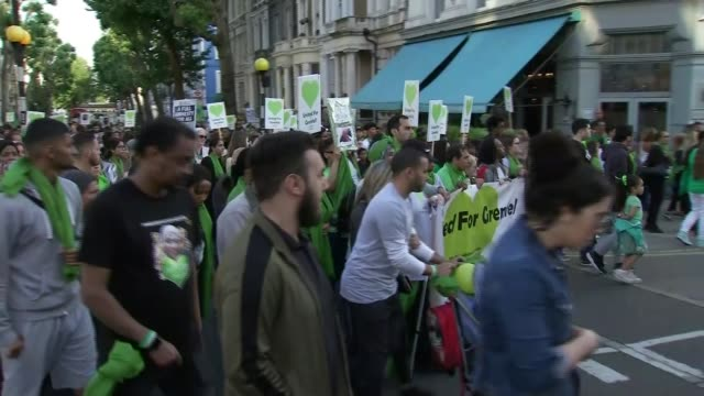 day of commemorations UK London Grenfell Tower fire anniversary silent march firefighters ENGLAND London North Kensington EXT Various of large crowd...