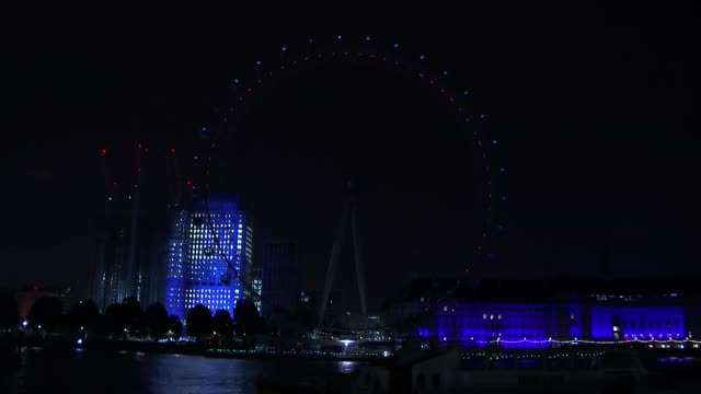 stockvideo's en b-roll-footage met day of commemorations uk london grenfell tower fire anniversary buildings illuminated with green light 10 downing street london eye silent march... - stille