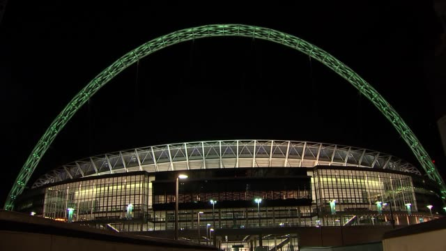 grenfell tower fire one year anniversary: wembley arch lit up with green light; england: london: wembley stadium: ext / night wembley arch lit up... - wembley stadium stock videos & royalty-free footage