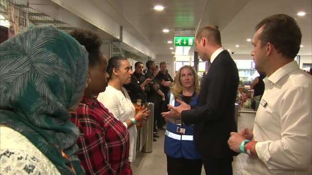 Prince William and the Queen visit Westway Sports Centre INT Queen Elizabeth II along past shoes on ground and boxes of donations / Queen chatting to...