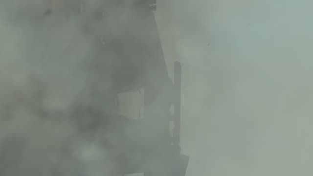 smouldering building and firefighters england london kensington ext various of smoke rising from grenfell tower block / church spire and charred... - fire hose stock-videos und b-roll-filmmaterial