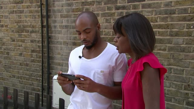 Survivor taunted by online trolls Oluwaseun Talabi and reporter watching video on mobile phone