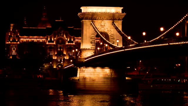 gresham palace & széchenyi chain bridge at night, budapest - széchenyi chain bridge stock videos and b-roll footage