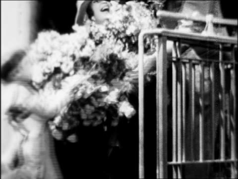 greta garbo getting off train with large bouquet of flowers / arrival in hollywood / newsreel - 1926 stock videos & royalty-free footage