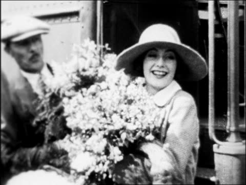 greta garbo standing by train with large bouquet of flowers / arrival in hollywood / newsreel - 1926 stock videos & royalty-free footage