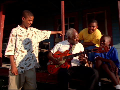 grey haired african american man plays red guitar to three boys, jackson, mississippi - blues stock videos & royalty-free footage