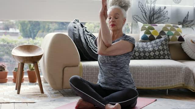 grey haired senior woman practising yoga in sitting room - serene people stock videos & royalty-free footage