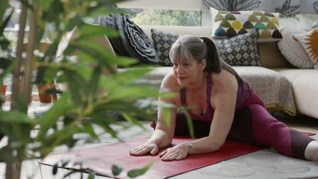 grey haired woman practising yoga at home - leotard stock videos & royalty-free footage