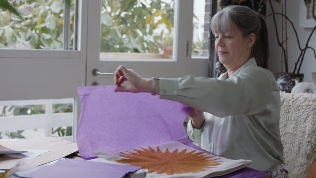 grey haired woman preparing materials at table - accuracy stock videos & royalty-free footage