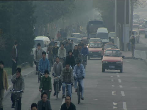 Grey hazy view of group of cyclists traveling towards camera on busy road with taxis and other traffic beside them Beijing