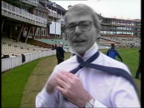Grey John Major on cricket pitch doing up his tie