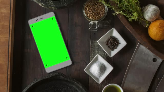 Grey Smartphone on Kitchen Table with Chroma Key Green Screen