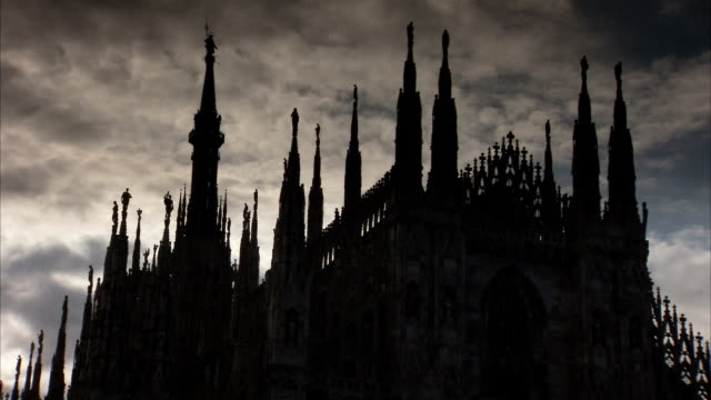 Grey storm clouds float over the intricate spires of the Milan Cathedral. Available in HD.