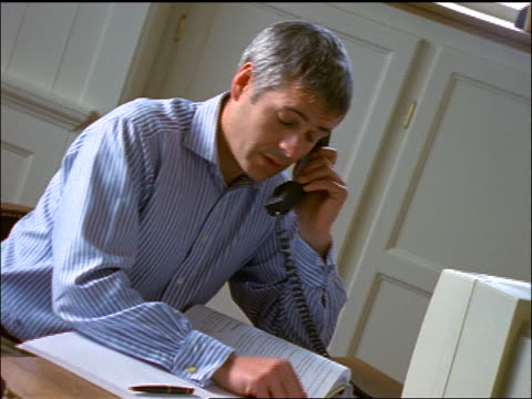 Grey-haired man talking on phone + working on computer at desk in home office