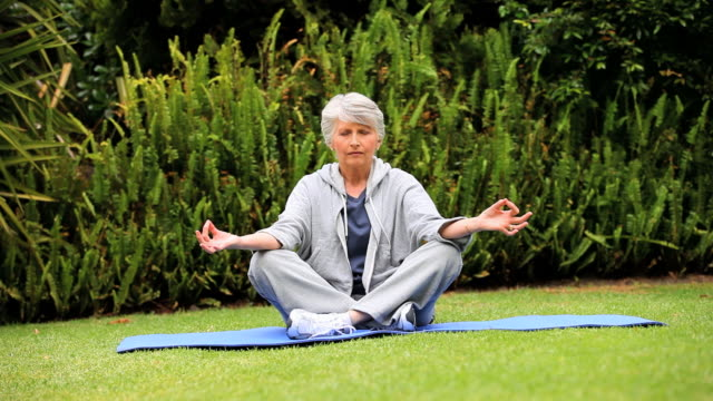 vídeos y material grabado en eventos de stock de grey-haired woman doing yoga in the garden / cape town, western cape, south africa - posición del loto