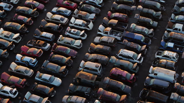 grid of cars in scrapyard at sunset - drone shot - large group of objects stock videos & royalty-free footage