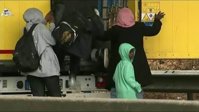 vidéos et rushes de gridlock on roads leading to channel ports; lib france: calais: port of calais: ext bv group of migrants clambering into back of lorry group of... - émigration et immigration