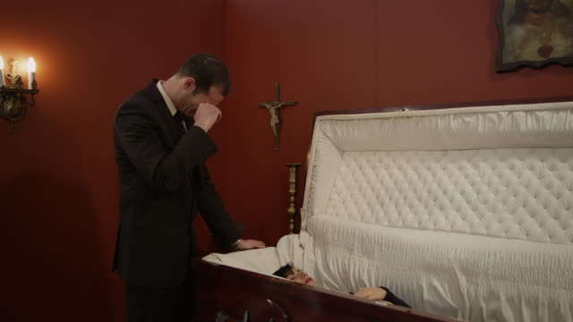 vidéos et rushes de a grieving man is surprised when his deceased loved one rises from her coffin - funérailles