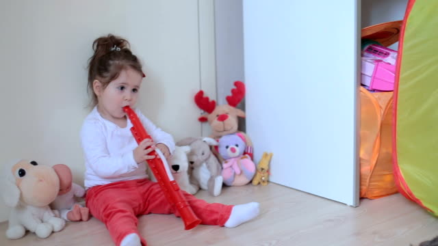 gril sitting among toys and perform with flute - nursery bedroom stock videos & royalty-free footage