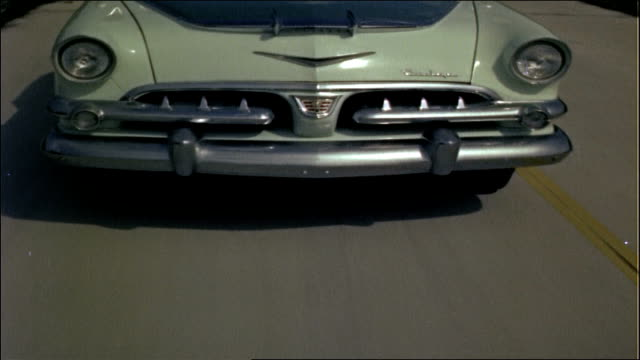 grille of green 1956 dodge custom royal sedan traveling on highway - autostrada interstatale americana video stock e b–roll
