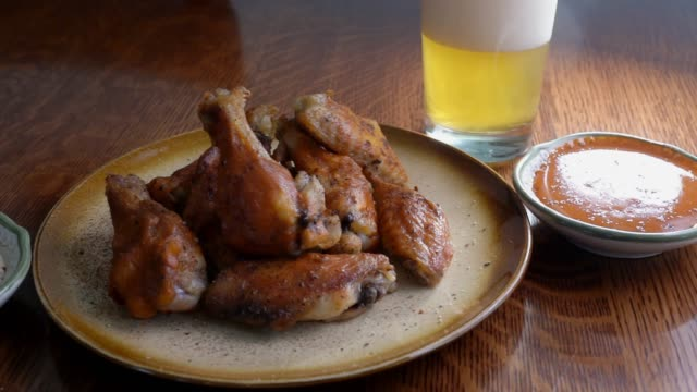 grilled baked chicken wings with hot wing sauce plated with sauce on the side and a beer - pollo video stock e b–roll