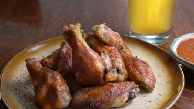 grilled baked chicken wings with hot wing sauce plated with sauce on the side and a beer - ranch dip stock videos & royalty-free footage