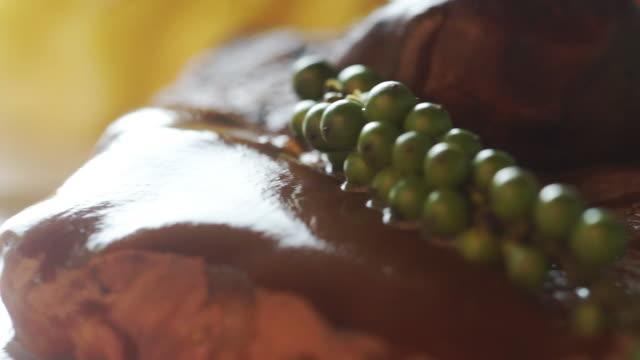vídeos de stock, filmes e b-roll de bife de carne grelhado com molho e os peppercorns verdes frescos na placa. - bbq sauce