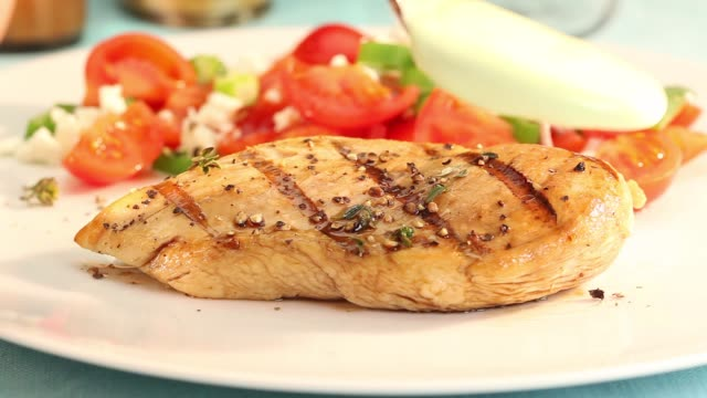 grilled chicken breast being served with a light sauce - pollo ai ferri video stock e b–roll