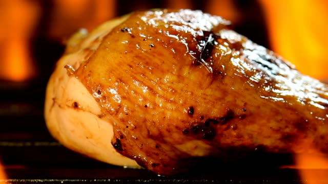 grilled chicken legs on the flaming grill - pollo alla brace video stock e b–roll