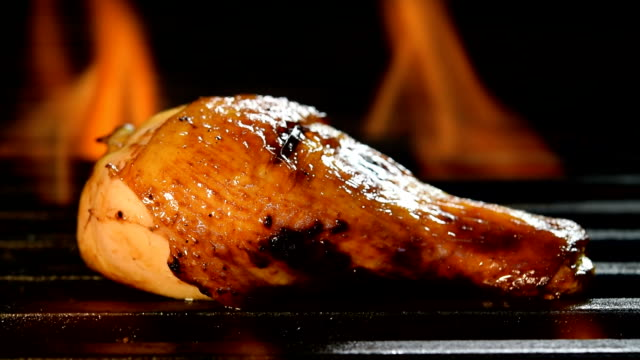 Grilled chicken legs on the flaming grill