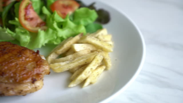 grilled chicken steak with vegetable salad and french fries