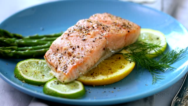 grilled fillet of salmon with asparagus served on a plate - plate stock videos & royalty-free footage
