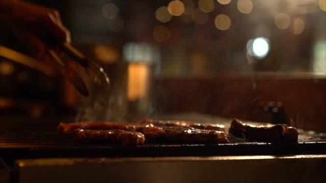 vídeos de stock e filmes b-roll de grilled meat /steak  on the flaming grill - bife