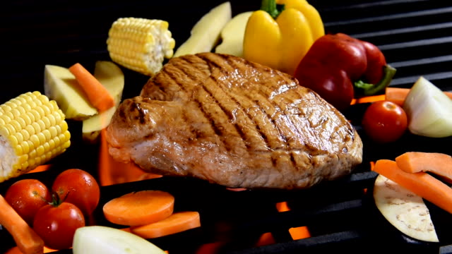 Grilled meat /steak with vegetable on a flaming grill