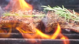 grilled meat with thyme. Roast meat, sprinkled with salt and fragrant pepper. A lot of fire and smoke On the meat is a fragrant sprig of thyme. Slow motion. Close up.;