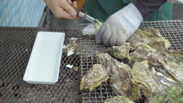 vídeos de stock, filmes e b-roll de grilled oyster street food in japan - bbq sauce