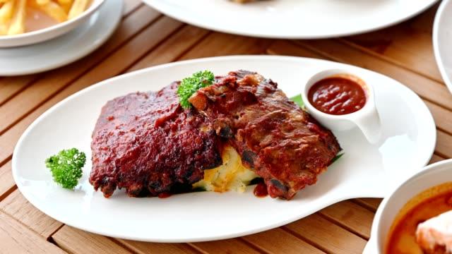 vídeos de stock, filmes e b-roll de reforços de carne de porco grelhados com molho do tempero na batata triturada na placa branca - bbq sauce
