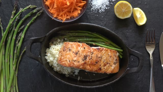 vídeos de stock e filmes b-roll de grilled salmon fillet with asparagus and cauliflower rice. - marisco