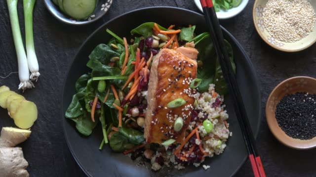 grilled salmon on a spinach salad with quinoa, carrots, cranberries, chickpeas, edemame, pumpkin seeds, and a ginger miso dressing. - preparing food stock videos & royalty-free footage