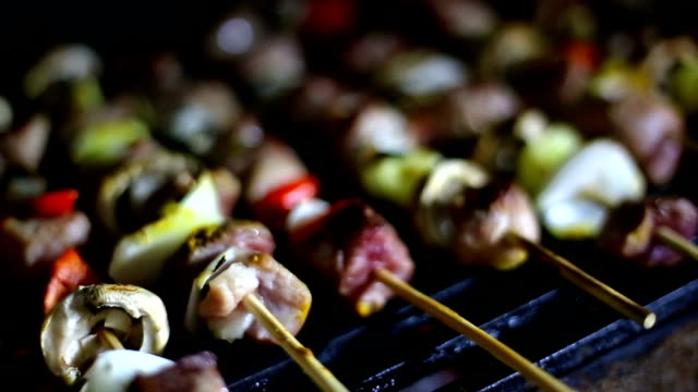 Grilled Skewers of sausage, mushrooms and onion on grill