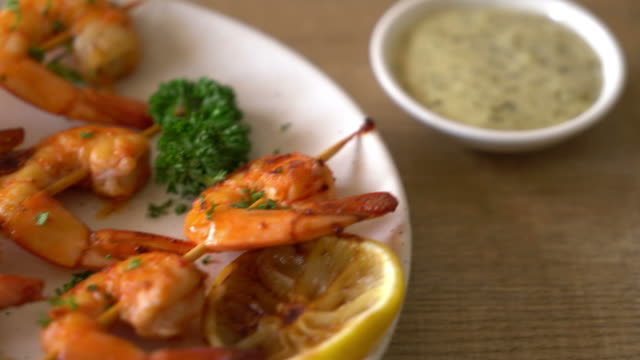 Grilled tiger shrimps skewers with lemon
