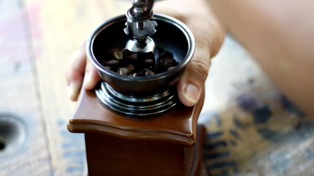 Grinding coffee beans with an old hand coffee grinder.
