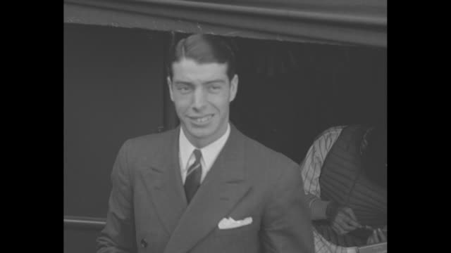 Grinning Joe DiMaggio wearing a suit smiles from New York Yankees dugout / CU DiMaggio in uniform smiling