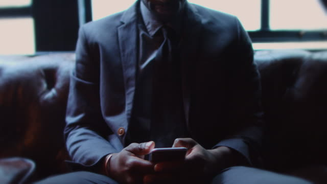 grinning man in suit looking at cell phone - 全套西裝 個影片檔及 b 捲影像
