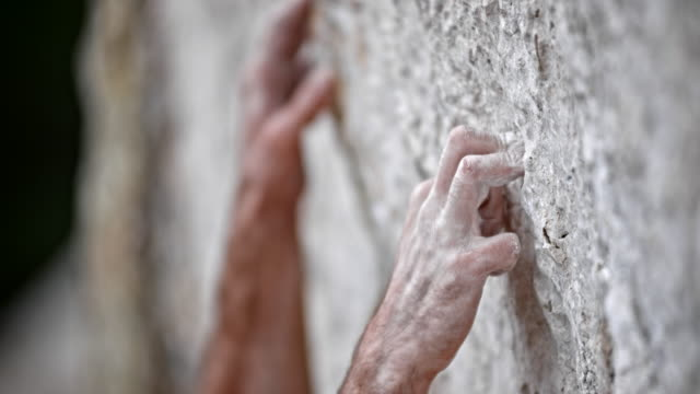 slo mo pan grip of a male rock climber's hand - climbing stock videos & royalty-free footage