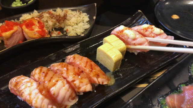 gripping grilled salmon sushi , bangkok , thailand. - grilled salmon stock videos & royalty-free footage