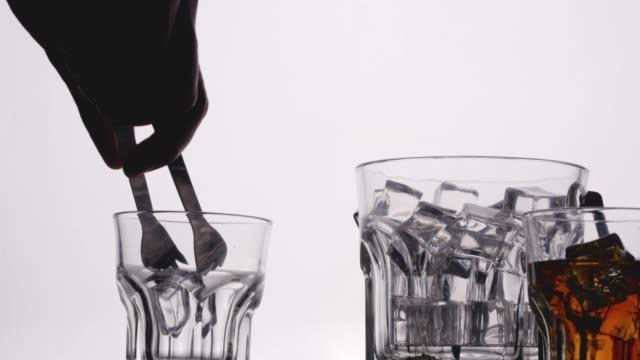 vídeos de stock e filmes b-roll de cu gripping ice cubes from bucket to  an empty glass. - copo vazio