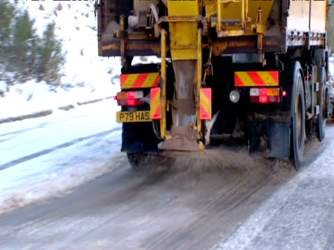 gritter lorry spreads grit onto snowy road scotland - mineral stock-videos und b-roll-filmmaterial