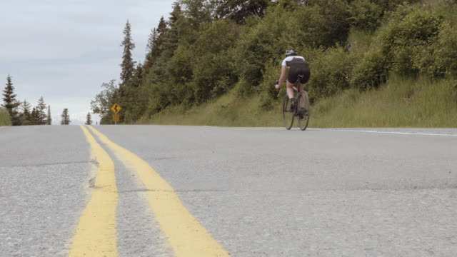 uhd 4k: gritty and competitive female cyclist training on a country road - fatcamera stock videos and b-roll footage